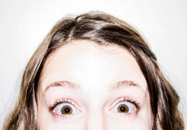 close-up of a woman's eyes looking shocked